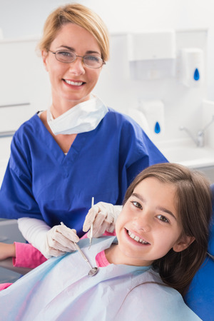 pediatric: Smiling pediatric dentist with a happy young patient in dental clinic Stock Photo