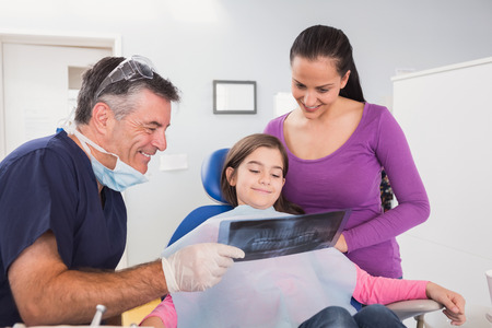 dental chair: Pediatric dentist explaining to mother and her daughter the x-ray in dental clinic