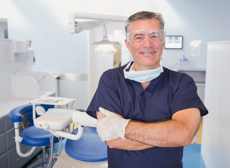 male dentist: Portrait of a smiling dentist with arms crossed in dental clinic Stock Photo