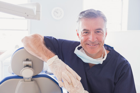 Smiling dentist leaning against dentists chair in dental clinic