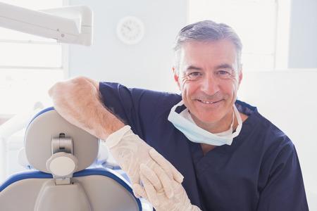 de higiene: Dentista sonriente que se inclina contra la silla de los dentistas en la cl�nica dental