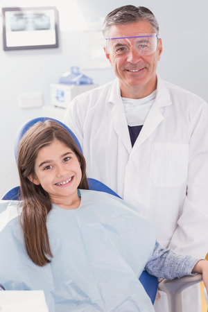 patient safety: Smiling dentist with safety glasses and happy young patient in dental clinic