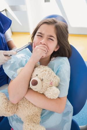 niño llorando: Boca cubierta paciente asustado y celebración de oso de peluche en la clínica dental