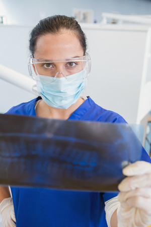surgical mask: Dentist wearing surgical mask and safety glasses studying the x-ray