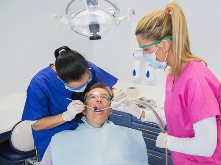 dental nurse: Dentist examining a patient with her dental nurse holding suction hose