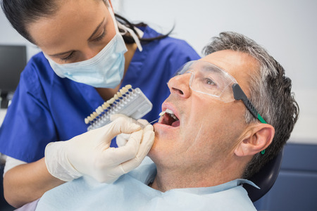 dental clinics: Dentist comparing teeth whitening of her patient in dental clinic