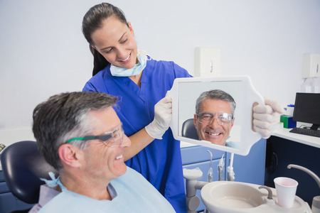 Smiling dentist showing teeth of her patient with a mirror in dental clinic