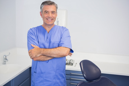 dentist: Smiling dentist standing with arms crossed in dental clinic