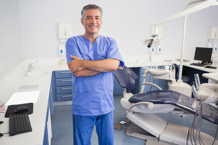 Happy dentist standing with arms crossed in dental clinic