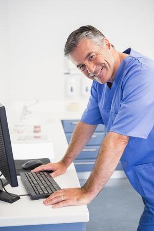 dentist: Portrait of a smiling dentist using computer in dental clinic Stock Photo