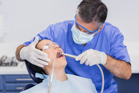 surgical mask: Dentist wearing surgical mask and safety glasses examining a patient