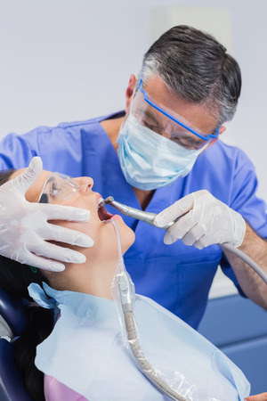 patient safety: Dentist wearing surgical mask and safety glasses examining a patient