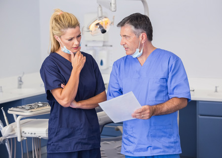 attentively: Thoughtful co-workers talking about a file attentively in dental clinic Stock Photo