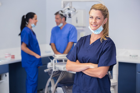 dental: Smiling nurse with arms crossed and co-workers behind her Stock Photo