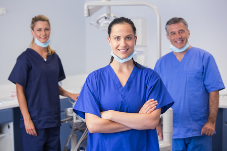 Portrait of smiling co-workers standing in dental clinic Stock Photo