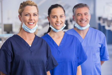 dentist mask: Portrait of smiling co-workers standing in a line in dental clinic Stock Photo