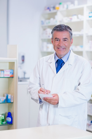 grey hair: Pharmacist with grey hair writing down notes in the pharmacy 스톡 사진
