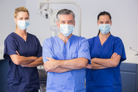 dental nurse: Co-workers wearing surgical mask with arms crossed in dental clinic