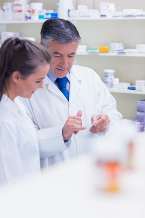 trainee: Pharmacist speaking with his trainee about prescription in the pharmacy