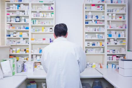 farmacia: Vista trasera de un farmac�utico que trabaja en batas de laboratorio en la farmacia Foto de archivo