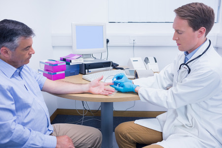 blood glucose meter: Doctor using a blood glucose meter at the hospital