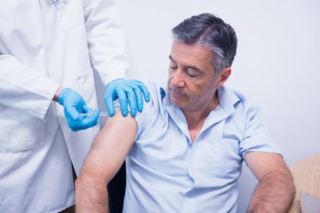 young adult men: Doctor giving injection to his patient at the hospital Stock Photo