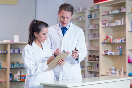 Trainee Holding A Prescription While Talking To The Pharmacist ...