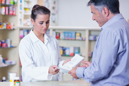 Customer handing a prescription to a trainee in the pharmacy photo
