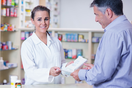 Customer handing a prescription to a smiling trainee in the pharmacy photo