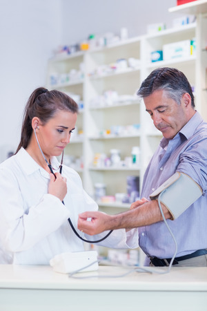 taking medicine: Trainee listening to patients pulse with stethoscope in the pharmacy Stock Photo