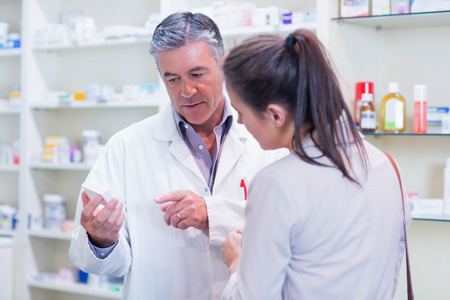 recetas medicas: Farmacéutico que habla con alegre cliente joven en la farmacia Foto de archivo