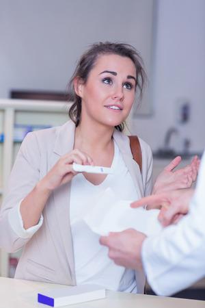 taken: Shocked woman holding pregnancy test in the pharmacy Stock Photo