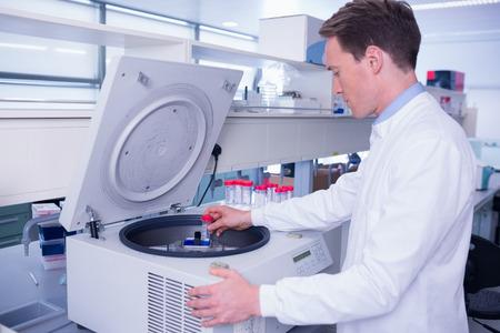 lab coat: Qu�mico en bata de laboratorio utilizando una centr�fuga de laboratorio