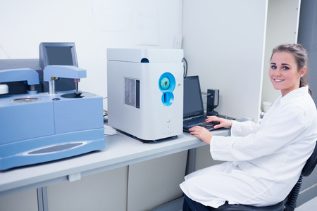biochemist: Smiling young biochemist using laptop at her desk in laboratory Stock Photo