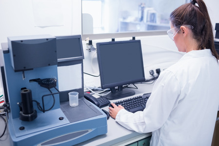 female scientist: Young scientist typing on his computer in laboratory