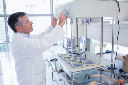 biotecnologia: Científico con gafas de seguridad utilizando la máquina en el laboratorio Foto de archivo