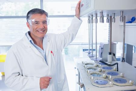 bata de laboratorio: Cient�fico sonriente con gafas de seguridad en el laboratorio