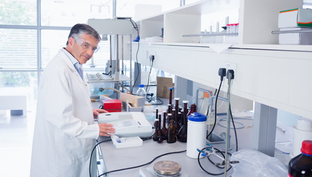 Scientist carrying out an experiment looking at the camera in laboratory