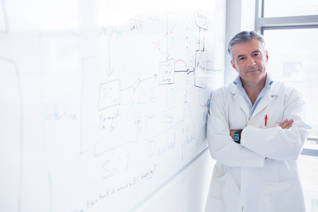 scientist man: Smiling scientist leaning against the whiteboard in laboratory Stock Photo