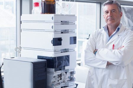 scientist: Scientist standing with arms crossed next to the machine in laboratory