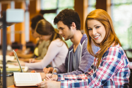 classmates: Student looking at camera while studying with classmates in library