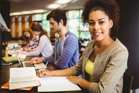 estudiando: Estudiante que mira a la c�mara mientras estudiaba con los compa�eros de clase en la biblioteca