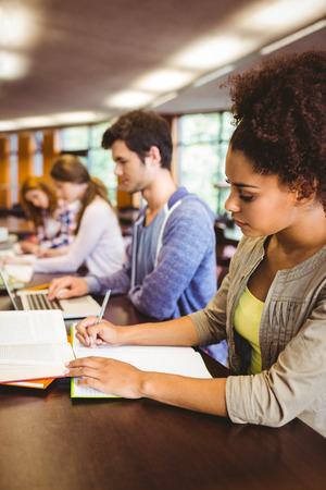 revision book: Focused students sitting in a line writing in library Stock Photo