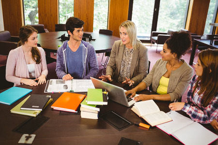 revision book: Smiling students working together on an assignment in library Stock Photo