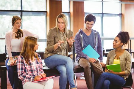 profesor: Estudiantes felices que hablan con su profesor en la biblioteca Foto de archivo