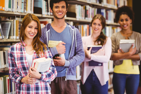 Happy students holding books in row in library photo
