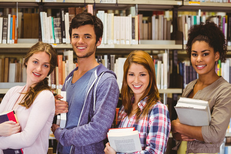 Students in a line smiling at camera holding books in library photo