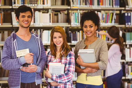 revision book: Students standing and smiling at camera holding books in library