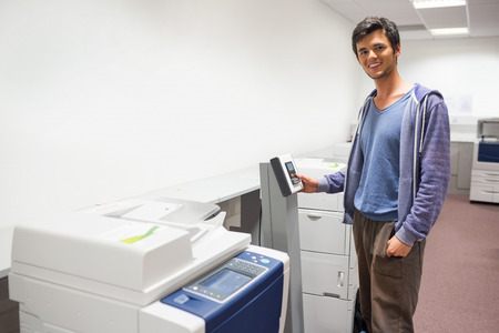 fotocopiadora: Estudiante sonriente de pie junto a la fotocopiadora en la universidad