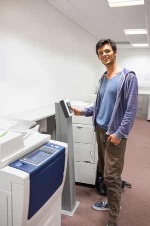 photocopier: Smiling student standing next to the photocopier at the university Stock Photo